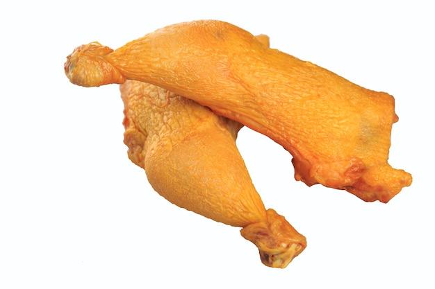 Muslos de pollo ahumado sobre un fondo blanco.