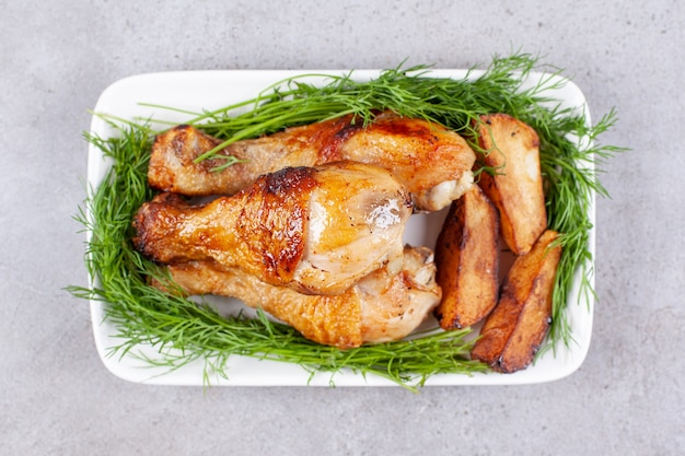 Muslos de pollo al horno con verduras en una placa blanca.