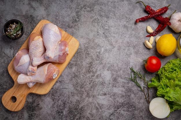 Muslos de pollo crudo crudo sobre la superficie oscura.