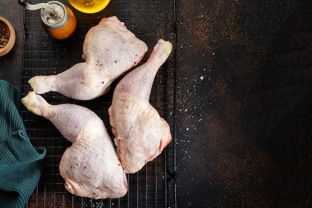 Muslos de pollo crudo con especias y sal en marrón.
