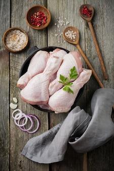 Muslos de pollo crudo en una olla de hierro fundido con especias y hierbas en madera vieja preparada para cocinar.