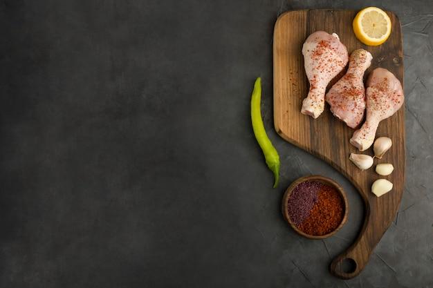 Muslos de pollo crudo servidos con limón y especias