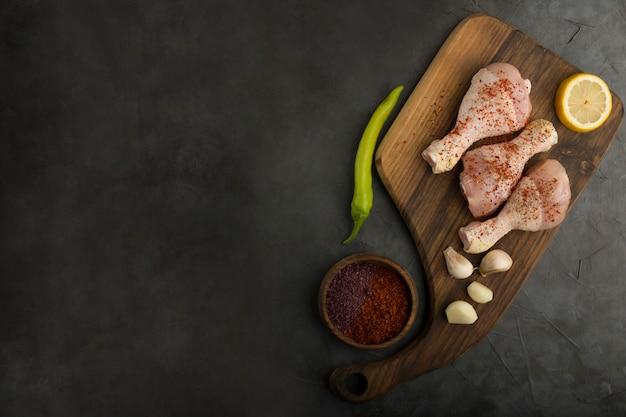 Muslos de pollo crudo servidos con salsas y limón