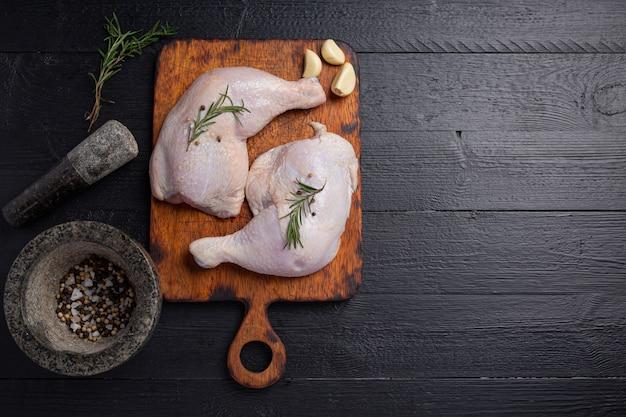 Muslos de pollo crudo sobre la superficie de madera oscura.