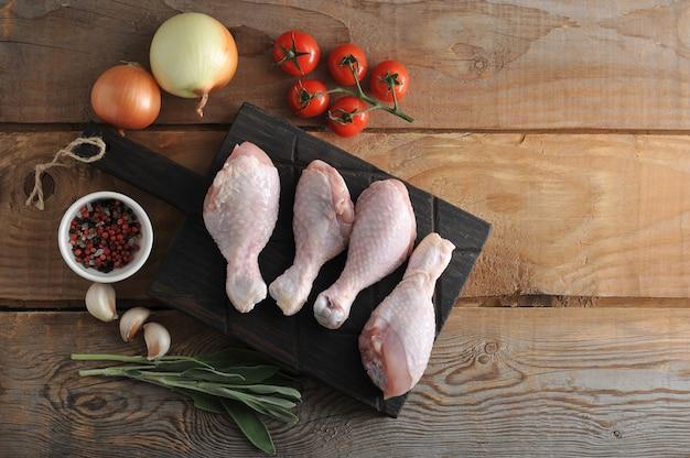 Muslos de pollo crudo sobre una tabla de madera, cebolla, ajo, especias y una ramita de romero
