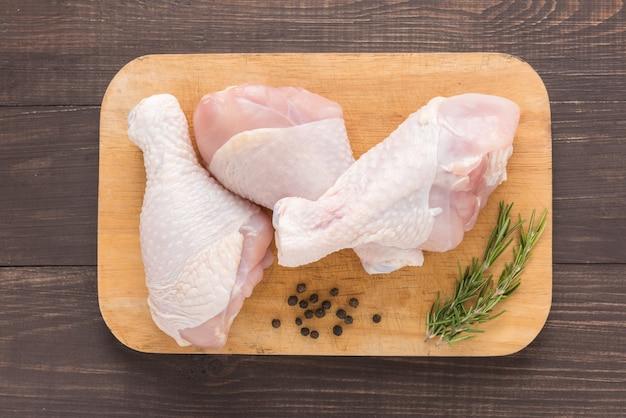 Muslos de pollo crudo en tabla de cortar en mesa de madera