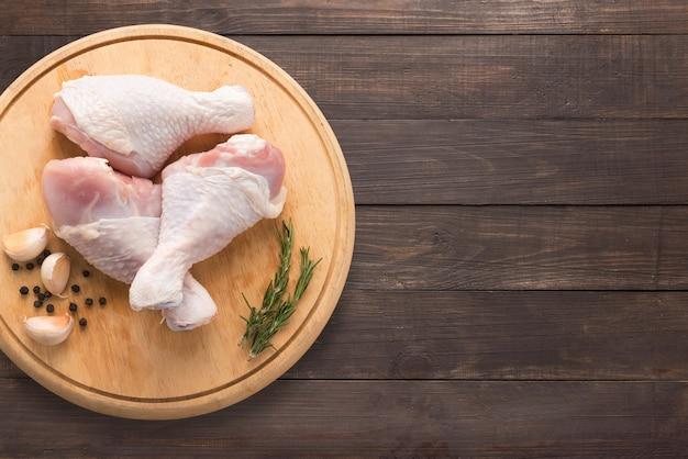 Muslos de pollo crudo en tabla de cortar sobre fondo de madera. copie espacio para su texto