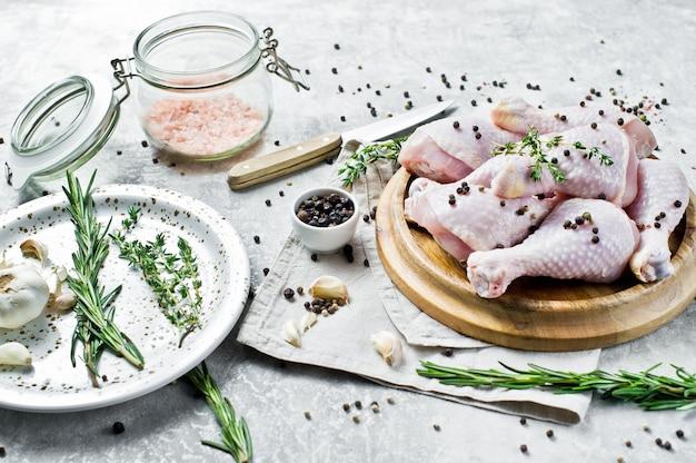Muslos de pollo crudos. ingredientes para cocinar: romero, tomillo, ajo, pimienta.