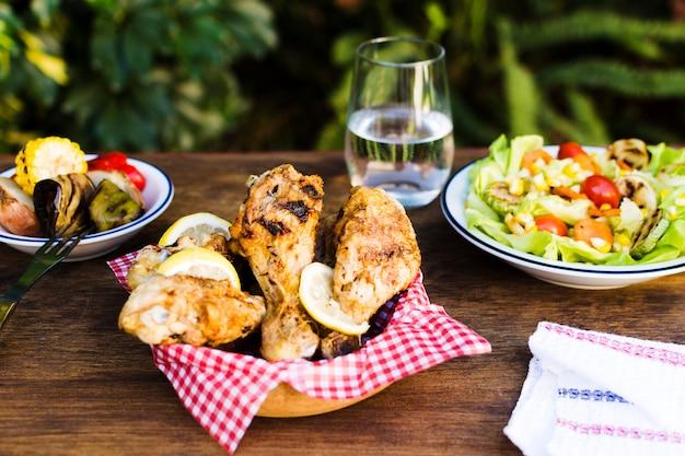 Muslos de pollo y ensalada al aire libre.