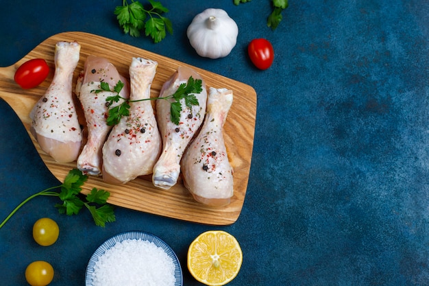 Muslos de pollo con especias y sal listos para cocinar en la tabla de cortar.
