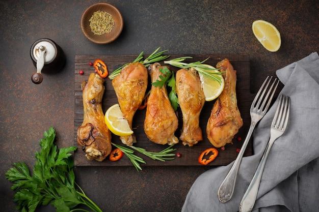 Muslos de pollo frito sobre tabla de cortar de madera sobre un fondo oscuro de hormigón o piedra