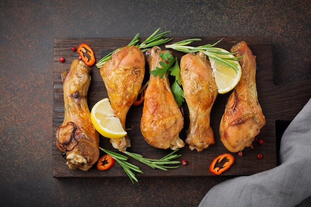 Muslos de pollo frito sobre tabla de cortar de madera sobre una superficie oscura de hormigón o piedra. enfoque selectivo