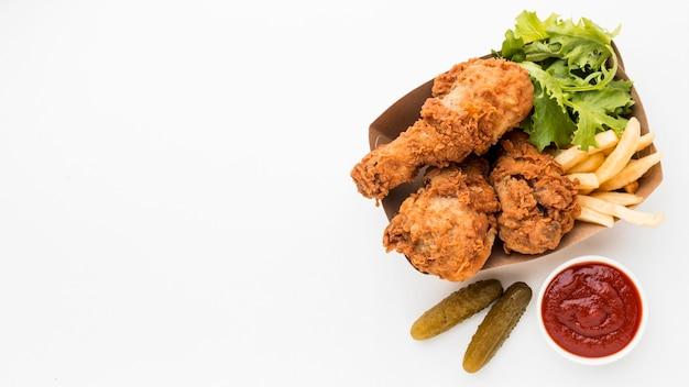 Muslos de pollo frito de vista superior con salsa de tomate y papas fritas con espacio de copia