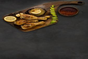 Muslos de pollo a la parrilla servidos con limón, chile y salsas