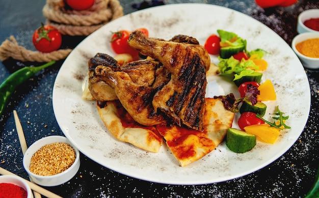 Muslos de pollo a la parrilla sobre pan de pita servidos con vegetales frescos
