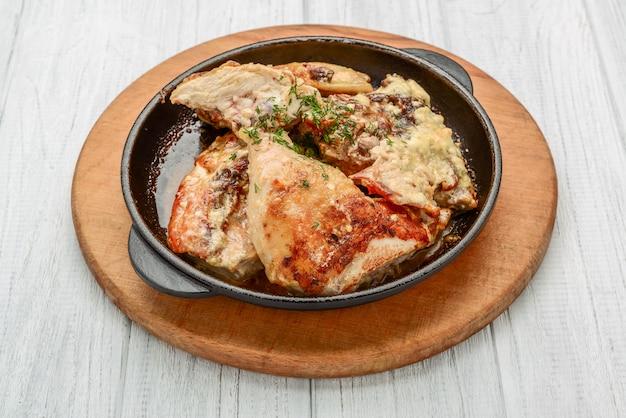 Muslos de pollo picantes al horno en salsa de ajo en una sartén de hierro fundido