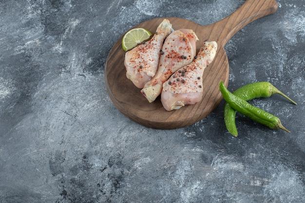 Muslos de pollo picantes y pimientos sobre fondo gris.
