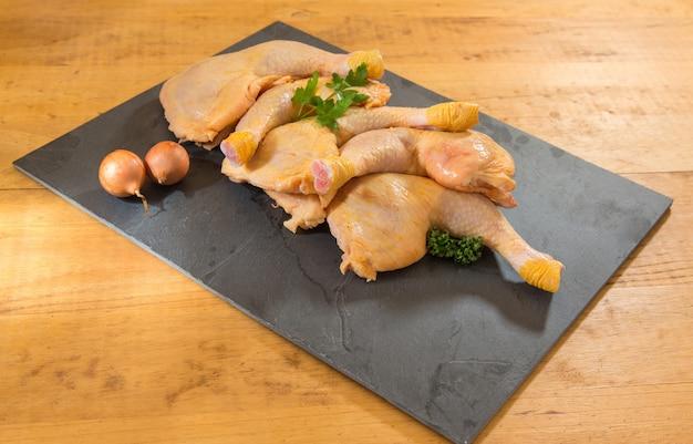 Muslos de pollo en una pizarra en una mesa de madera