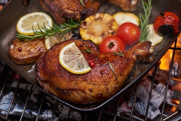 Muslos de pollo a la plancha a la parrilla en llamas con verduras asadas con tomates, patatas, semillas de pimiento, sal.