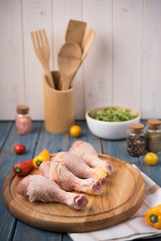 Muslos de pollo sobre tabla de madera con pimientos