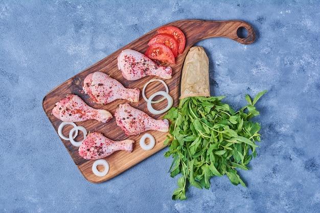 Muslos de pollo con verduras sobre una tabla de madera en azul