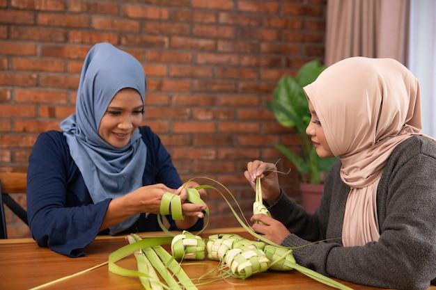 Musulmanes haciendo ketupat tradicional o pastel de arroz