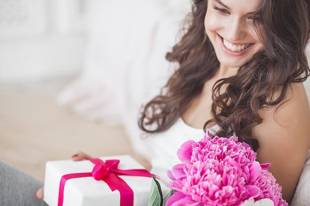 Muy bella mujer con flores y regalos en el interior