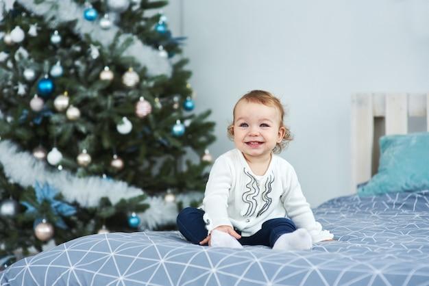 Muy bonita y encantadora niña rubia vestida de blanco sentada en la cama y mirando la imagen en el fondo de sonrientes árboles de navidad en el brillante interior de la casa