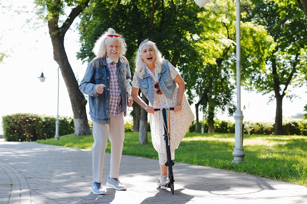 Muy divertido. mujer feliz alegre que usa un scooter mientras está en el parque junto con su esposo