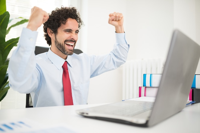 Muy feliz hombre de negocios mirando su computadora