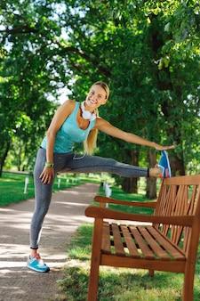 Muy flexible. encantado de mujer positiva sonriendo mientras pone su pierna en el banco