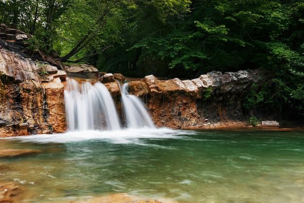 Muy hermosa cascada de primavera en el valle del río jean en el bosque
