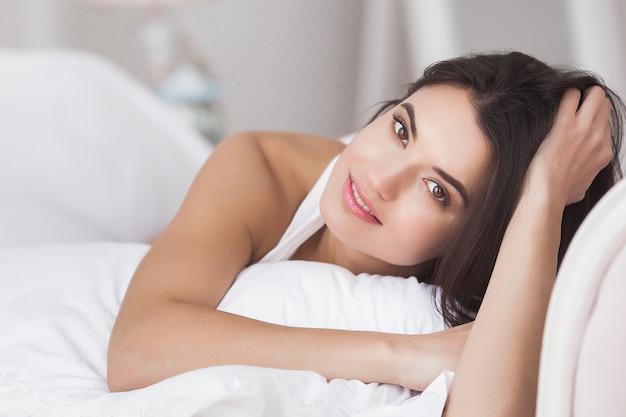Muy hermosa mujer en la cama. retrato de joven atractiva en el dormitorio