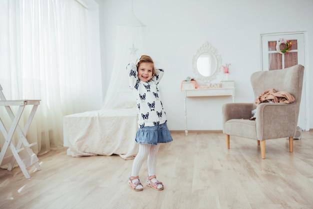 Muy hermosa rubia encantadora niña de pie en el brillante interior de la casa, a la vista