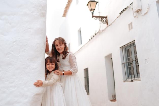 Muy hermosas hermanas caucásicas, vestidas con traje de comunión y la niña con un vestido blanco con una flor, en unas calles con paredes blancas del pueblo gaditano