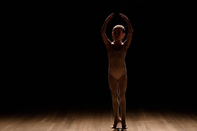 Muy joven bailarina posando sobre un fondo negro