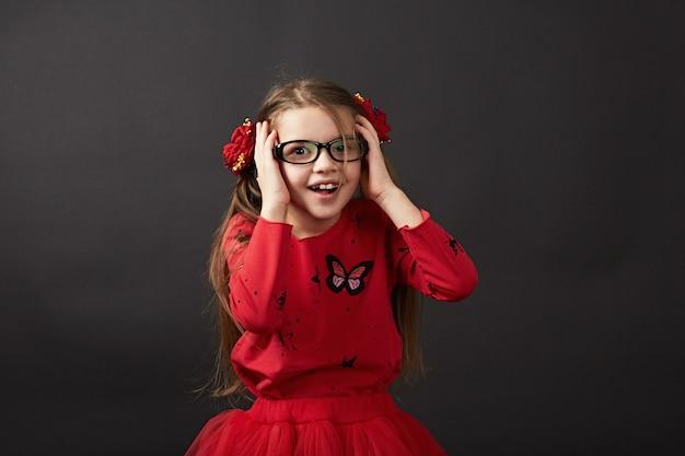 Muy linda chica mira a través de los lentes ligeramente sosteniendo su mano
