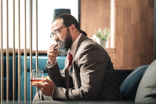 Muy nervioso. hombre de negocios próspero maduro barbudo fumando puros mientras se siente muy nervioso