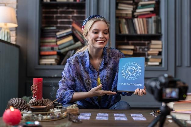 Muy recomendable. bonita mujer alegre apuntando al libro mientras habla de él en la cámara