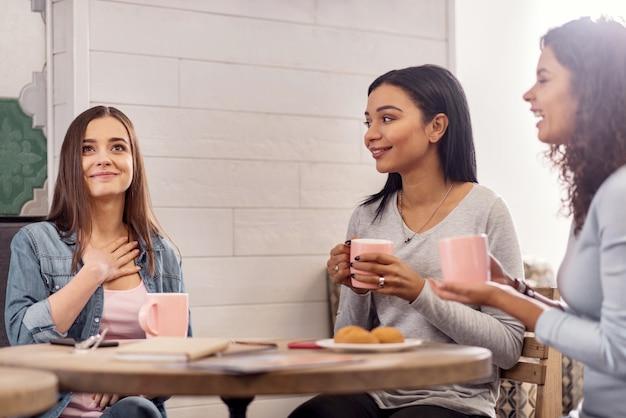 Muy romantico. hermosos y agradables tres amigos saliendo a tomar el té sentados en la mesa y comunicándose