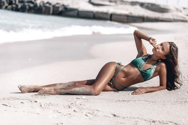 Muy sexy mujer bronceada con cabello castaño en bikini verde tumbada en la playa, toca seductoramente sus labios