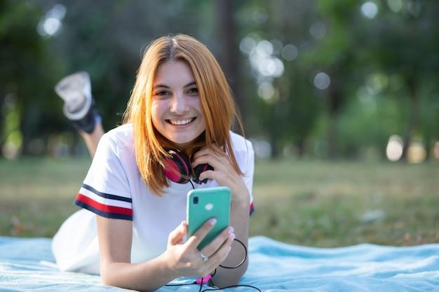 Muy sonriente adolescente con el pelo rojo con sellphone al aire libre en el parque.