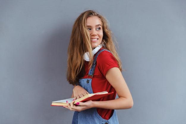 Muy sonriente adolescente sosteniendo libro