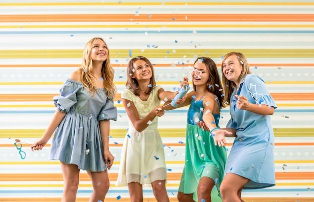 Muy sonriente chicas adolescentes en vestidos alegremente corriendo badajos en la fiesta de cumpleaños