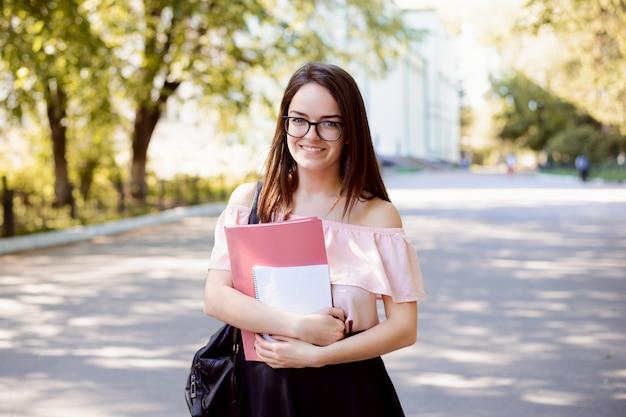 Muy sonriente estudiante vistiendo gafas y ropa casual con libros va a la universidad a la conferencia