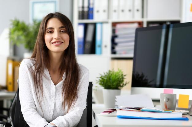 Muy sonriente pm o empleado sentado en la mesa de trabajo