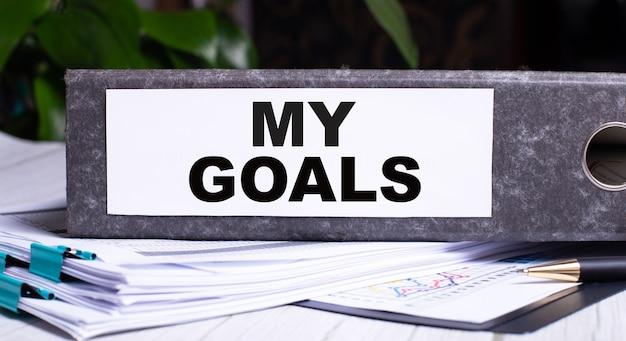 My goals está escrito en una carpeta de archivo gris junto a los documentos. concepto de negocio