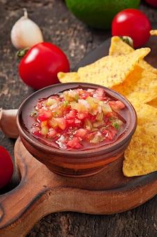 Nacho chips y salsa mexicana en un tazón de madera