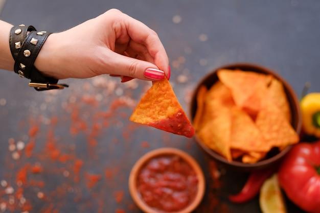 Nacho chips de tortilla frita casera. delicioso bocadillo de comida salada. mujer mano sujetando crujientes triangulares picantes bañados en salsa salsa de tomate