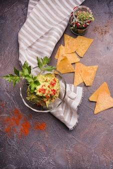 Nachos cerca de guacamole en un tazón y servilleta